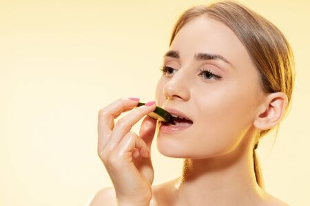 Photo for Close up of beautiful young woman with cucumber slice on yellow background. Concept of cosmetics, makeup, natural and eco treatment, skin care. Shiny and healthy skin, fashion, healthcare. - Royalty Free Image