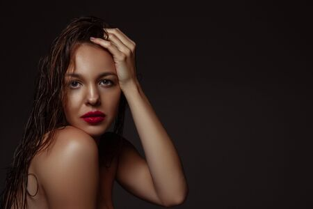 Photo pour Lovely. Portrait of beautiful stylish woman isolated on dark studio background. Caucasian model with red lipstick, wet hair and shiny skin, bright make up. Beauty, fashion, emotions concept. - image libre de droit