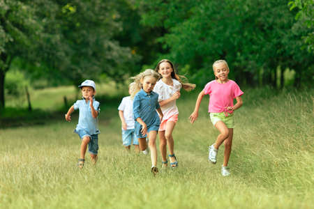 Photo for Kids, children running on meadow in summers sunlight. Look happy, cheerful with sincere bright emotions. Cute caucasian boys and girls. Concept of childhood, happiness, movement, family and summer. - Royalty Free Image