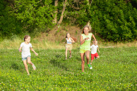 Photo pour Kids, children running on meadow in summers sunlight. Look happy, cheerful with sincere bright emotions. Cute caucasian boys and girls. Concept of childhood, happiness, movement, family and summer. - image libre de droit
