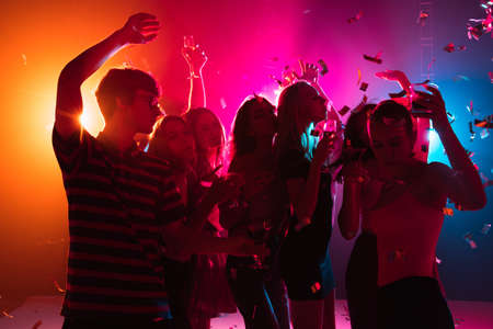 Photo pour Wild. A crowd of people in silhouette raises their hands, dancing on dancefloor on neon light background. Night life, club, music, dance, motion, youth. Bright colors and moving girls and boys. - image libre de droit