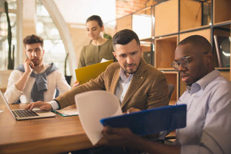 Photo for Colleagues working together in modern office using devices and gadgets during creative meeting - Royalty Free Image