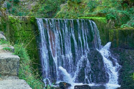 Waterfall at Source du Doubs Mouthe Franche Comté France with Green Plants On A Sunny Day