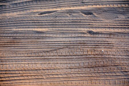 Photo pour Tracks Of Car Tires In The Sand Near A Beach Parking Area At Sunset - image libre de droit