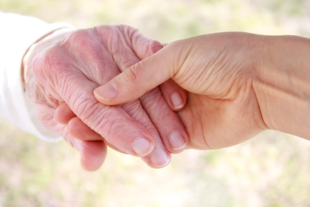 Young hand holding senior's hand