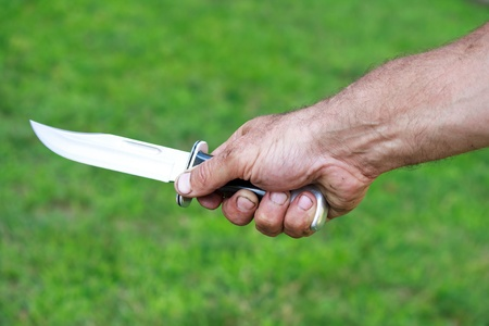 Man holding dagger over green lawn background
