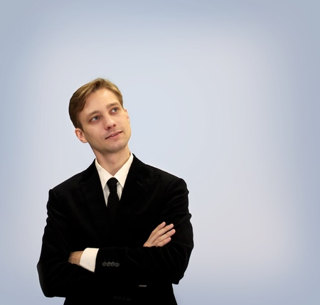 Young business in black suit looking upwards and thinking