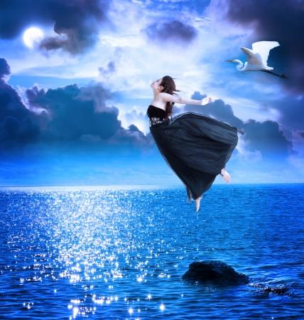 Foto de Beautiful girl jumping into the blue night sky with white egret - Imagen libre de derechos
