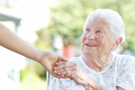 Happy senior woman holding hands with caretaker