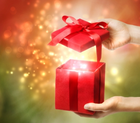 Photo for Woman holding a red gift box on a bright holiday lights background  - Royalty Free Image