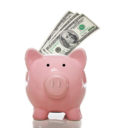 Pink piggy bank with 3 one hundred US dollar bills on a white background