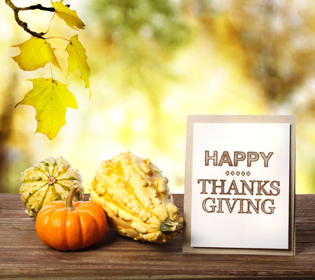 Happy Thanksgiving message card with pumpkins over yellow leaves