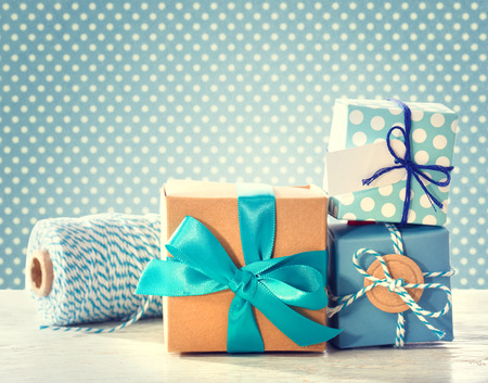Light blue handmade gift boxes over polka dots background