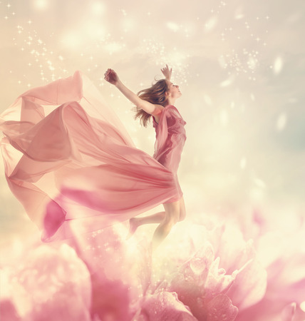 Beautiful young woman jumping on a giant flowerの写真素材