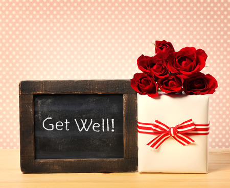Get Well message written on little chalkboard with roses and present box