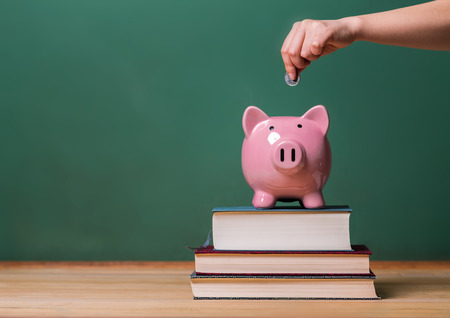 Foto de Person depositing money in a pink piggy bank on top of books with chalkboard in the background as concept image of the costs of education - Imagen libre de derechos