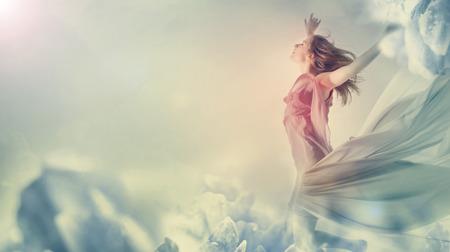 Photo pour Beautiful young woman jumping on a giant flower - image libre de droit