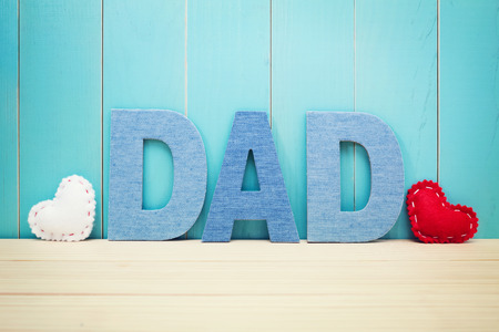 DAD text letters with white and red hearts over blue wooden background