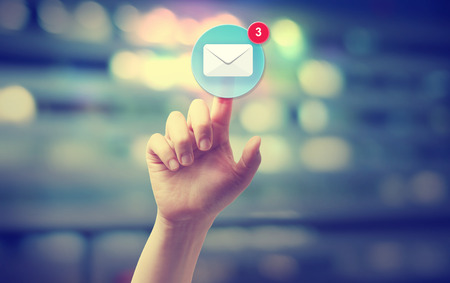 Hand pressing an email icon on blurred cityscape background