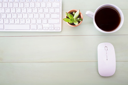 Neat workstation on a wooden desk viewed from overhead with a wireless computer mouse and keyboard, cup of coffee and houseplant
