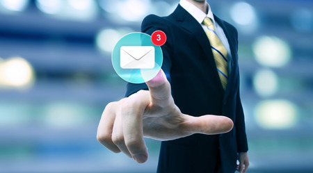 Businessman pointing at an email icon on blurred city background