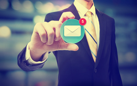 Business man holding an email icon on blurred cityscape background