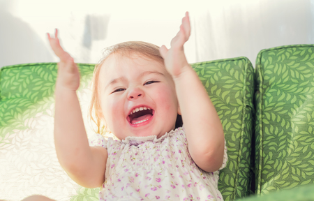 Photo pour Happy toddler girl smiling and clapping her hands - image libre de droit