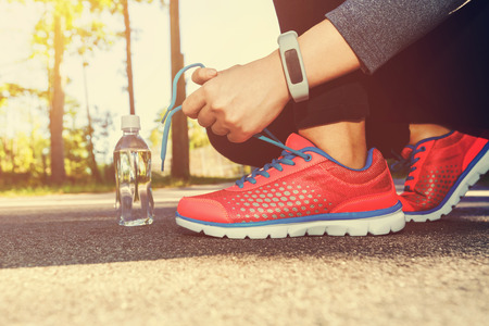 Foto de Female jogger tying her running shoes outside - Imagen libre de derechos