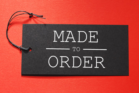 Made to Order text on a black tag on a red paper background