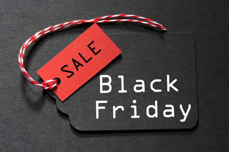 Black Friday Sale text on a black tag with a red and white twine