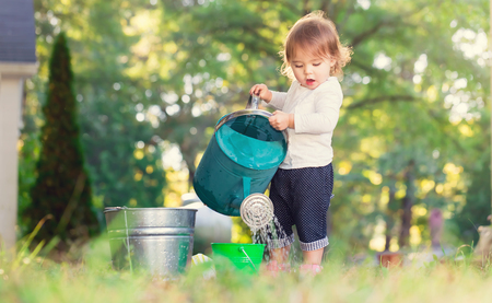 Foto de Happy toddler girl playing with watering cans outside - Imagen libre de derechos