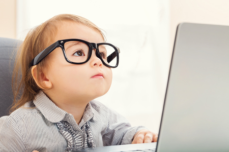 Photo pour Smart little toddler girl wearing big glasses while using her laptop - image libre de droit