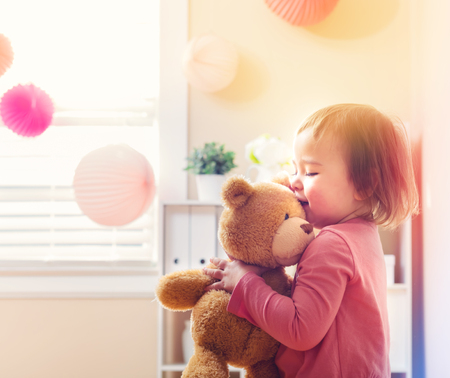 Photo pour Happy toddler girl playing with her teddy bear at house - image libre de droit
