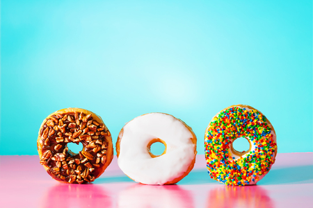Assorted donuts on pastel blue and pink background