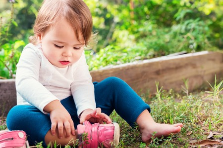 Photo pour Toddler girl putting on her sneakers outside - image libre de droit