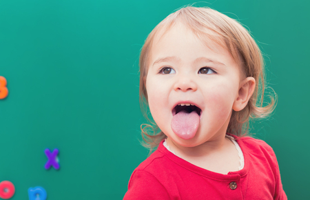Photo for Happy toddler girl sticking her tongue out in front of a green chalkboard - Royalty Free Image
