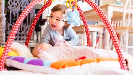 Foto de Happy toddler girl playing with her newborn sister - Imagen libre de derechos