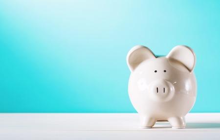 Photo pour White piggy bank isolated on blue background - image libre de droit