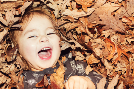 Photo pour Happy toddler girl smiling while lying down in big pile of leaves - image libre de droit