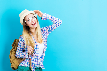 Photo for Happy young traveling woman on a blue background - Royalty Free Image