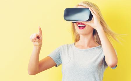 Photo pour Happy young woman using a virtual reality headset - image libre de droit