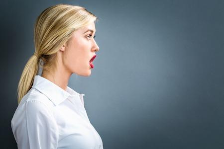 Photo pour Profile of a young woman on a gray background - image libre de droit