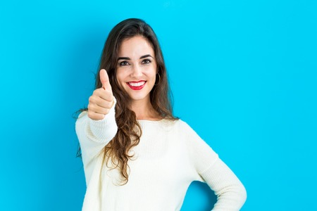 Photo pour Happy young woman giving a thumb up on a blue background - image libre de droit