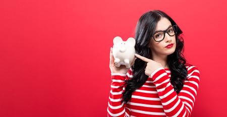 Photo pour Young woman with a piggy bank on a red background - image libre de droit