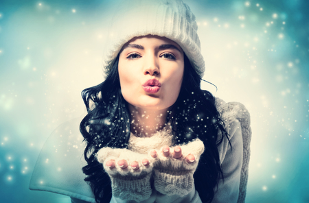 Happy young woman with winter clothes blowing a kiss