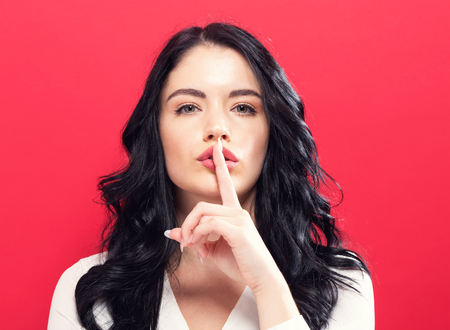 Photo for Young woman making a quiet gesture on a solid background - Royalty Free Image