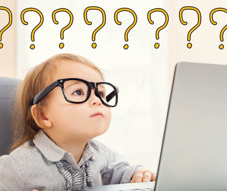 Photo pour Question Marks text with toddler girl using her laptop - image libre de droit