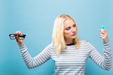 Photo pour Young woman choosing between contact lenses or glasses on a solid background - image libre de droit