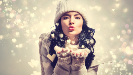 Photo pour Happy young woman with winter clothes blowing snow and hearts - image libre de droit