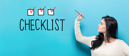 Foto de Checklist with young woman holding a pen on a blue background - Imagen libre de derechos